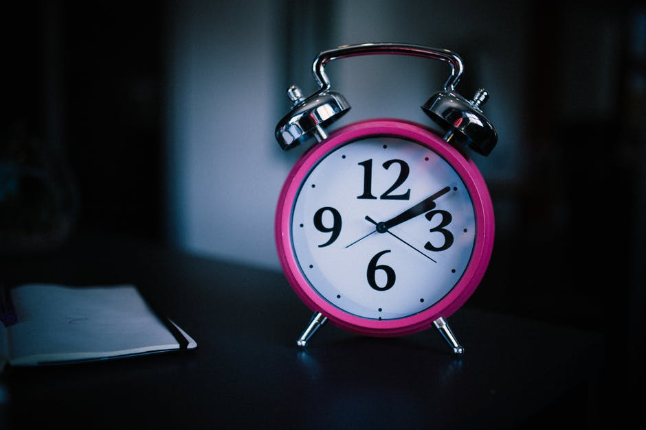 Pink clock sits on a table
