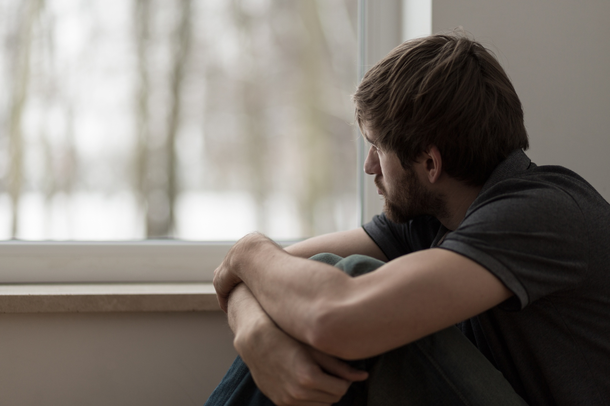 Young man with depression looking out a window