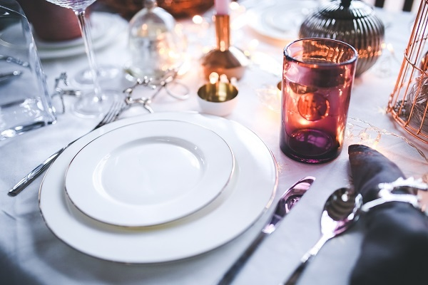 An all-white modern formal dinner place setting. Takes you to