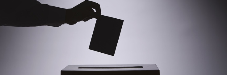 Person dropping ballot into box