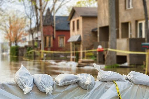Bags of sand in front of a row of houses damaged by floods