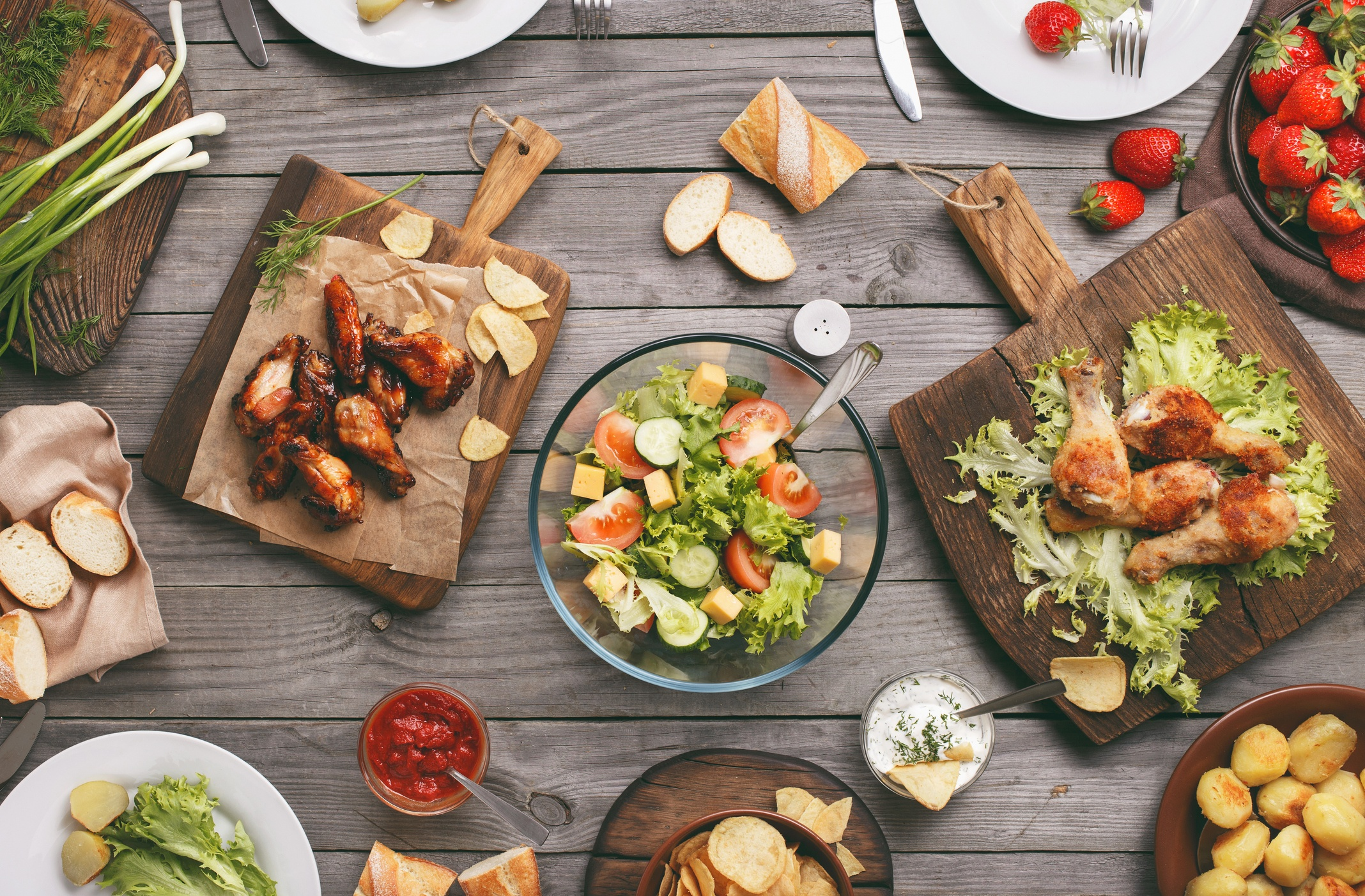 Chicken, salad, fruit, dips and bread on a table outside.