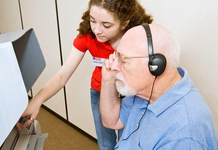 Young election volunteer explaining the new touch screen voting machine to a vision impaired man