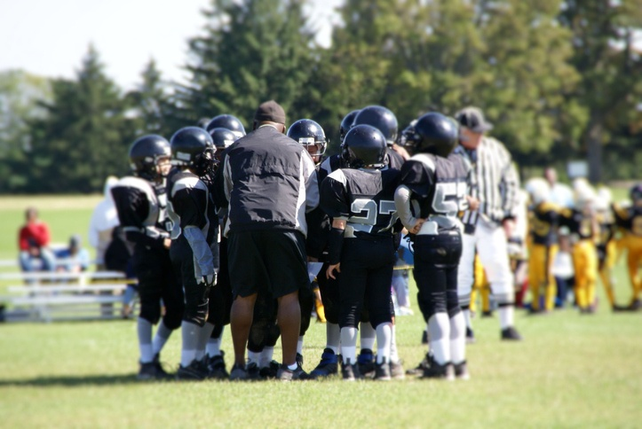 Youth huddle on a football field