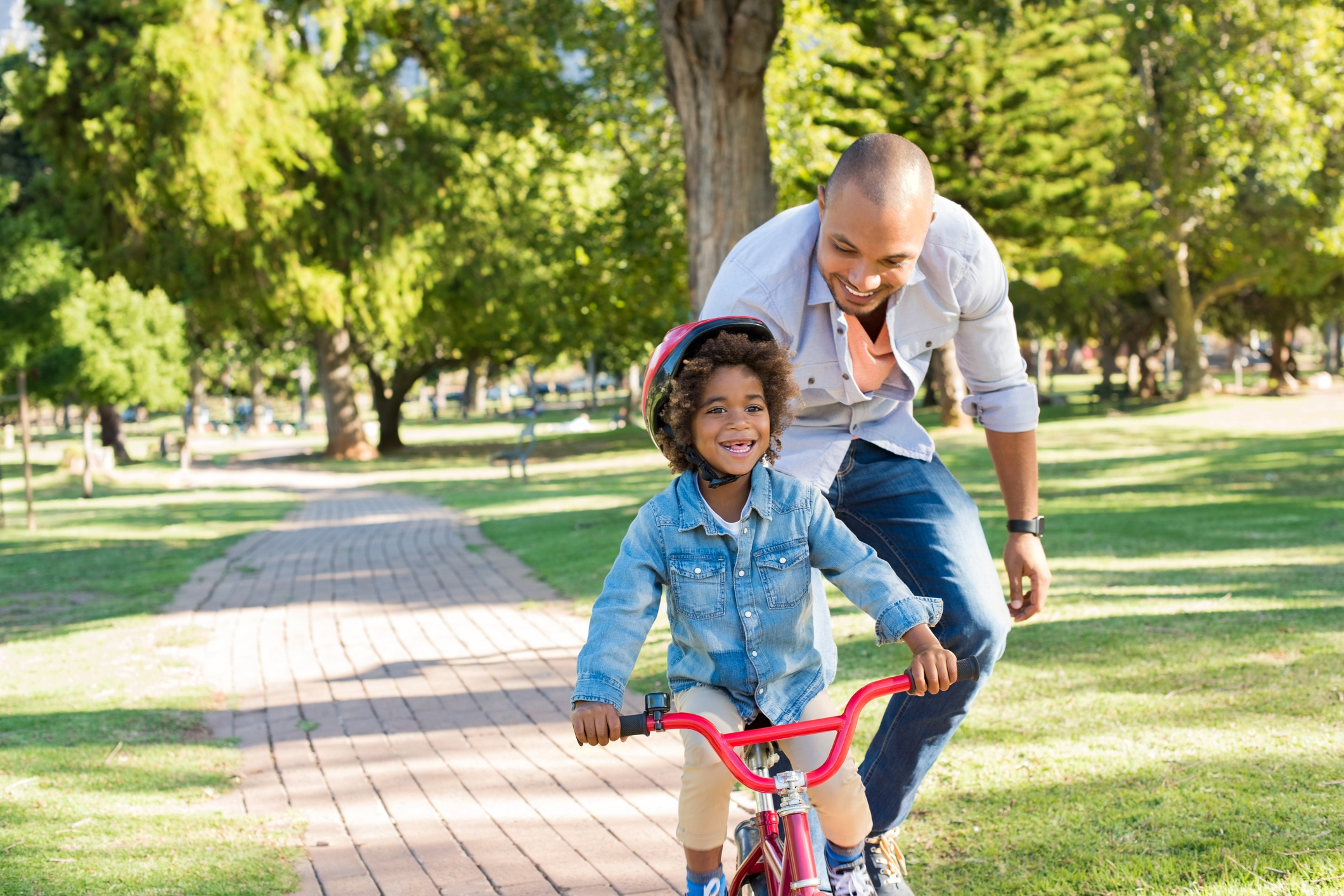 Father teaching son cycling in a park