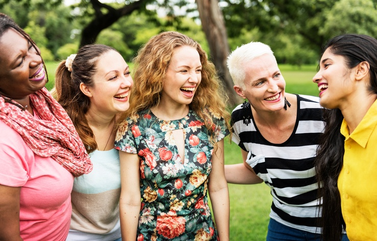 Group of five women laughing outdoors