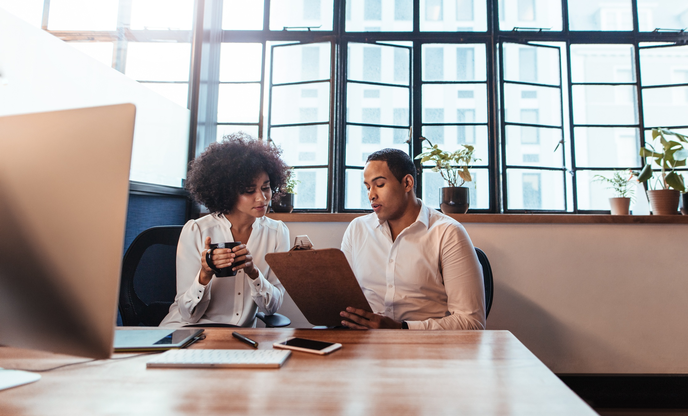 Two small business employees working at a desk looking at a clipboard
