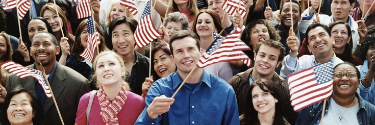 Diverse group of people waving American flags