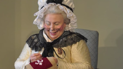 Martha Washington sewing in a chair. Link takes you to Kids.gov's video on Martha Washington.