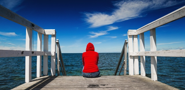 Person sitting in a pier starting at the ocean.