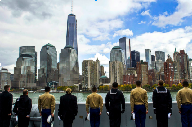 Navy servicemembers with hats off look onto New York City and the World Trade Center