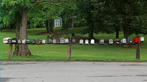 Row of mailboxes in front of a house and forest on the side of a street