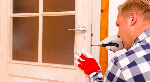 Handyman screwing a door handle into a door frame