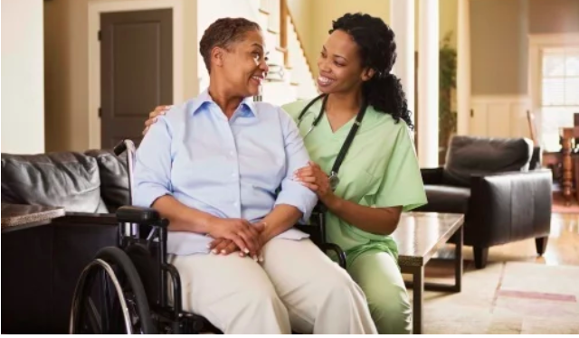 Nurse and woman in a wheelchair smile at each other in living room area during home visit