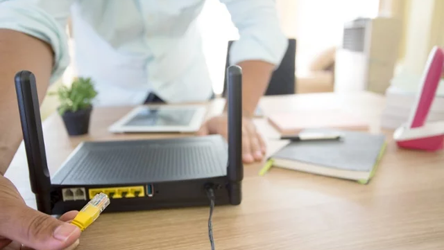 Person plugging in a home office router