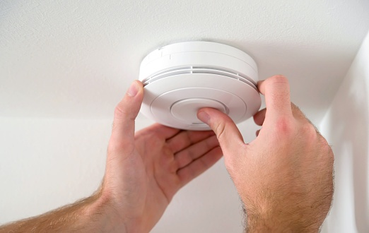 Hand adjusting smoke detector on ceiling