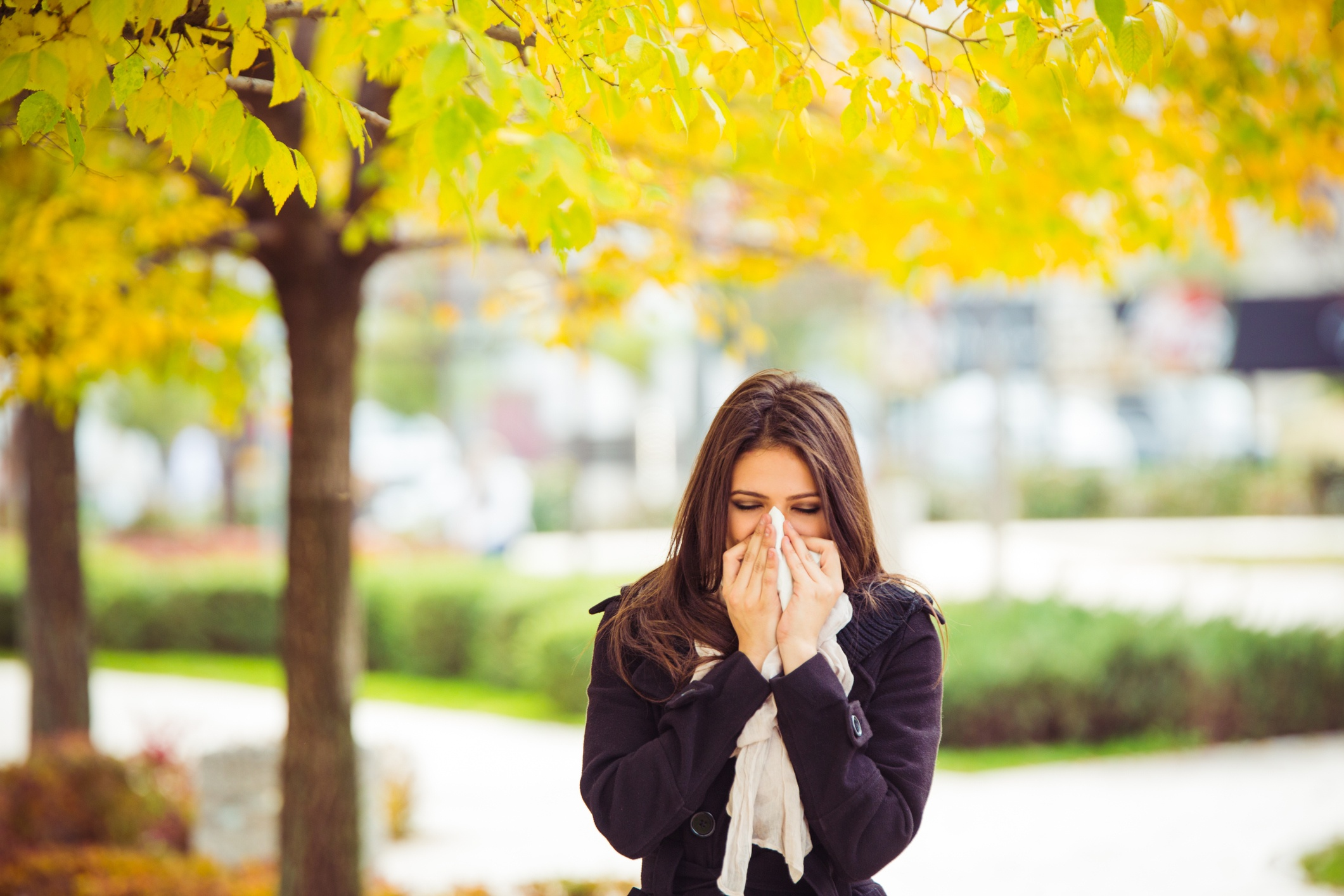 Woman blowing her nose in front of trees