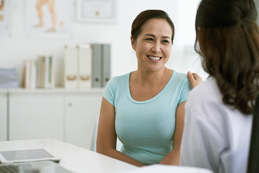 Woman talking to her doctor in a medical office.