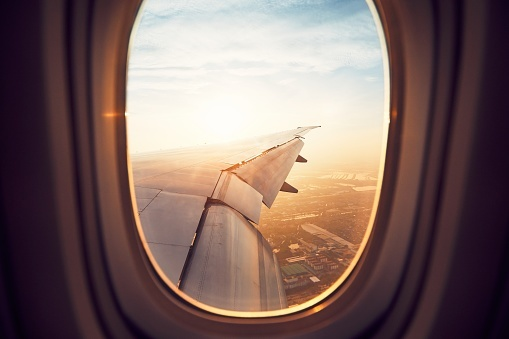 Looking out a plane window on to the wing in flight