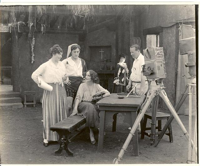 A black and white image of early 20th Century filmmaker Lois Weber and actors shooting a movie.