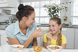 Mother and daughter eat breakfast. Link takes you to Kidsheath's page on breakfast.