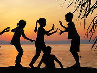 A silhouette of children playing by water. Link goes to NIH's page to reduce screen time.