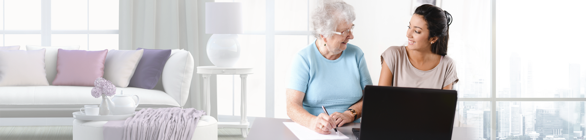 A young home health aide helps an older lady fill out paperwork