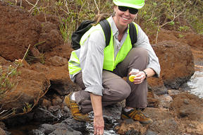 Zoologist Ellen Strong poses near a river. Link goes to Smithsonians's ScienceHow webcast.