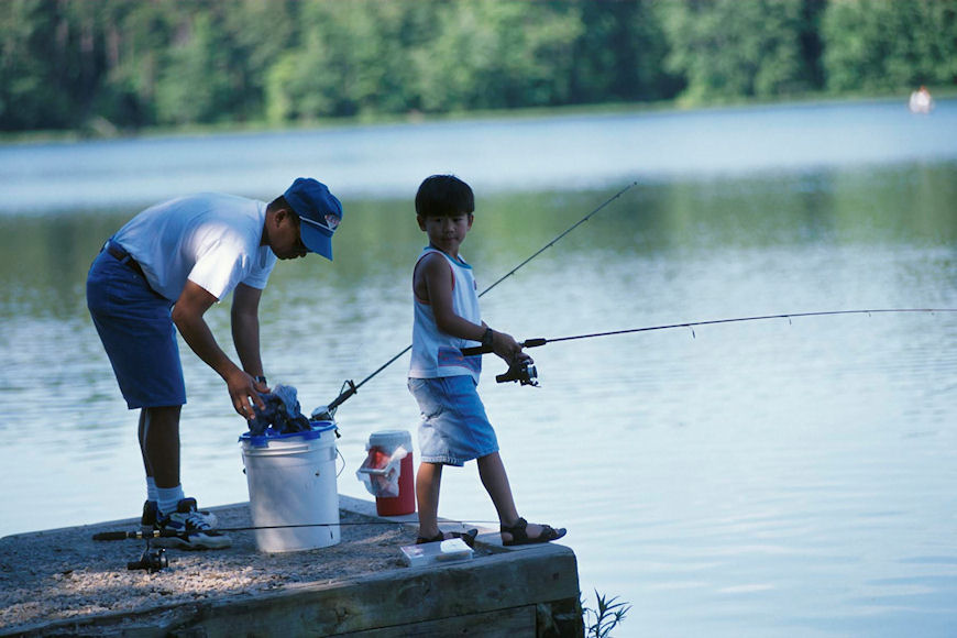 A boy fishes with his father. Link goes to Fish and Wildlife Services page on Special Events.