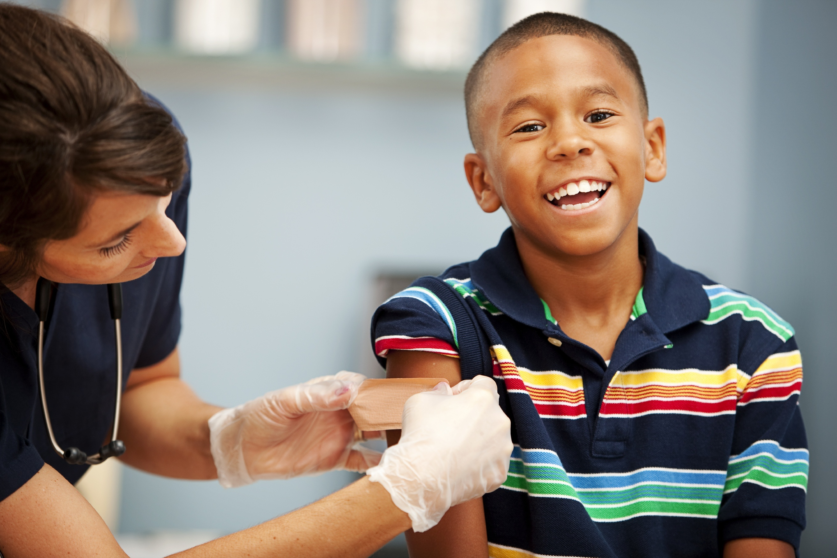 Little boy smiles while getting a bandaid after receiving his flu shot