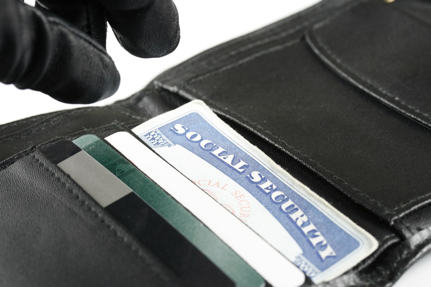A gloved thief reaches for a Social Security card in a stolen wallet