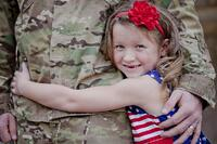 A military child hugs her parent. Link goes to DODEA's page on Military Children.