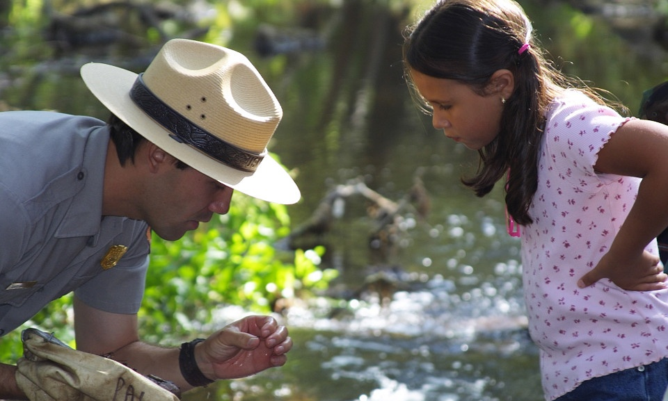 A park ranger shows a young girl a specimen of a plant near a creek.