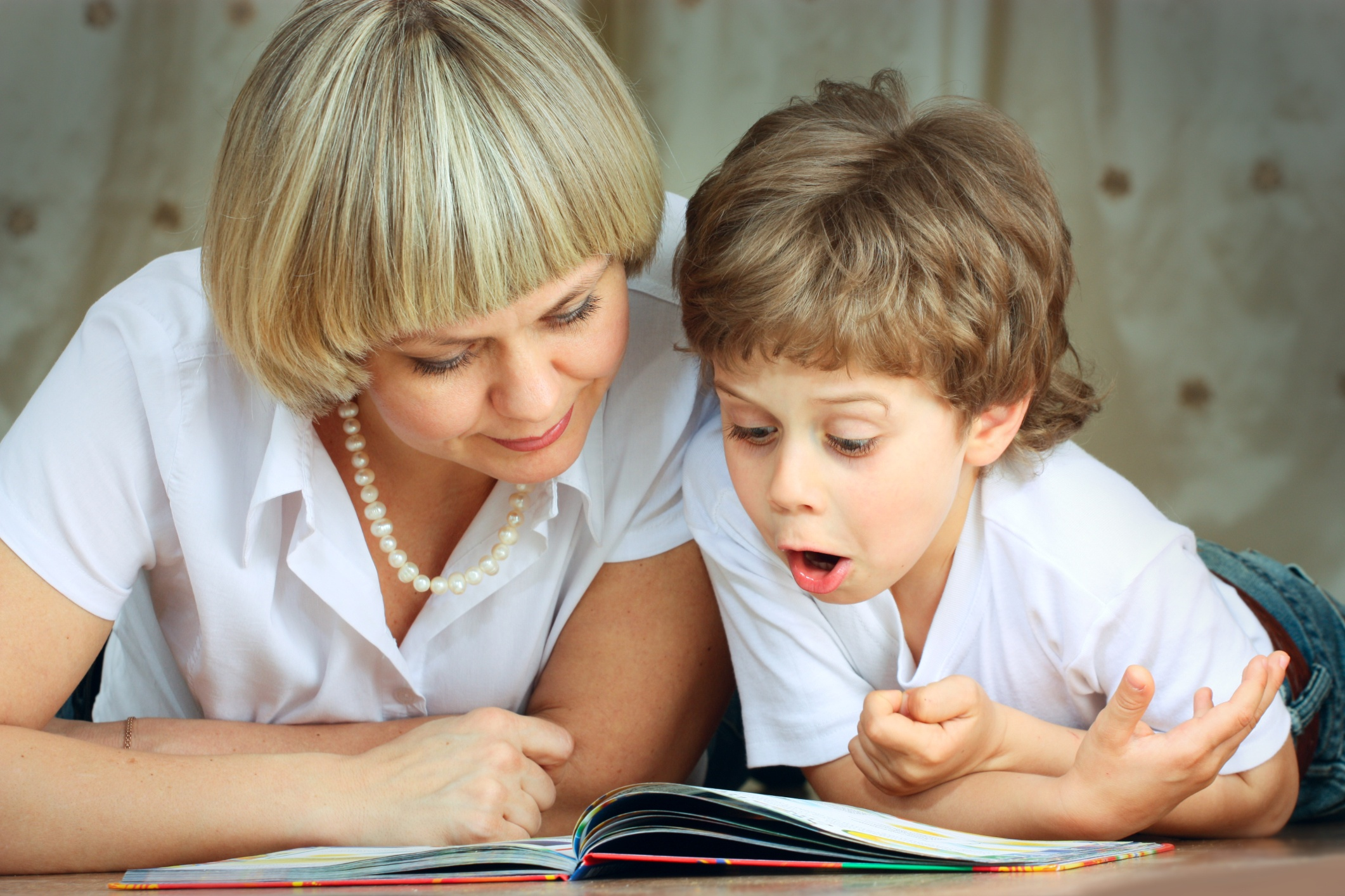 A mother and child read together. Link goes to CDC's Amazing Books for children.