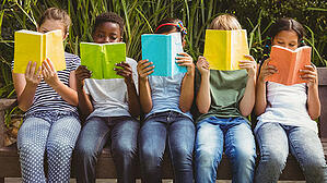 A row of children read books. Link goes PBS' page on summer learning.