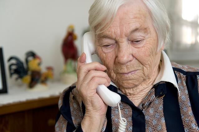 A senior lady holds a corded phone up to her ear in her living room.