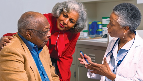 Older couple discusses with a doctor in her office