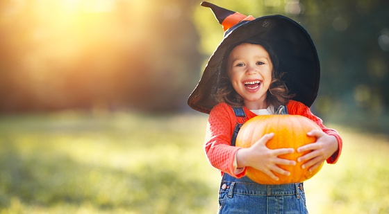 Young girl in a witch's hat smiling and holding a pumpkin