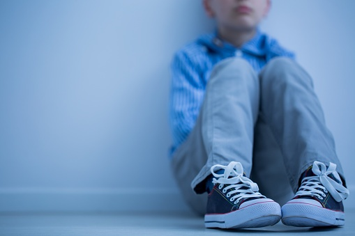 Child sitting against wall.
