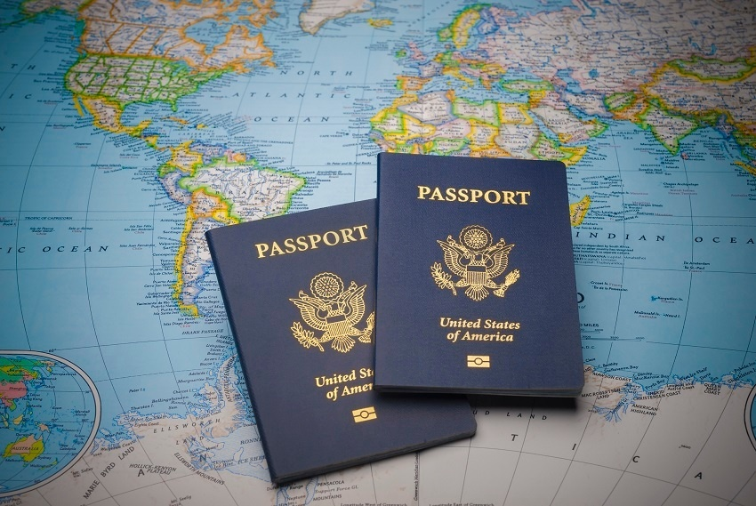 Two U.S. passports laid upon each other on top of a world map