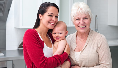 A young, smiling woman holds a baby beside an older smiling woman.