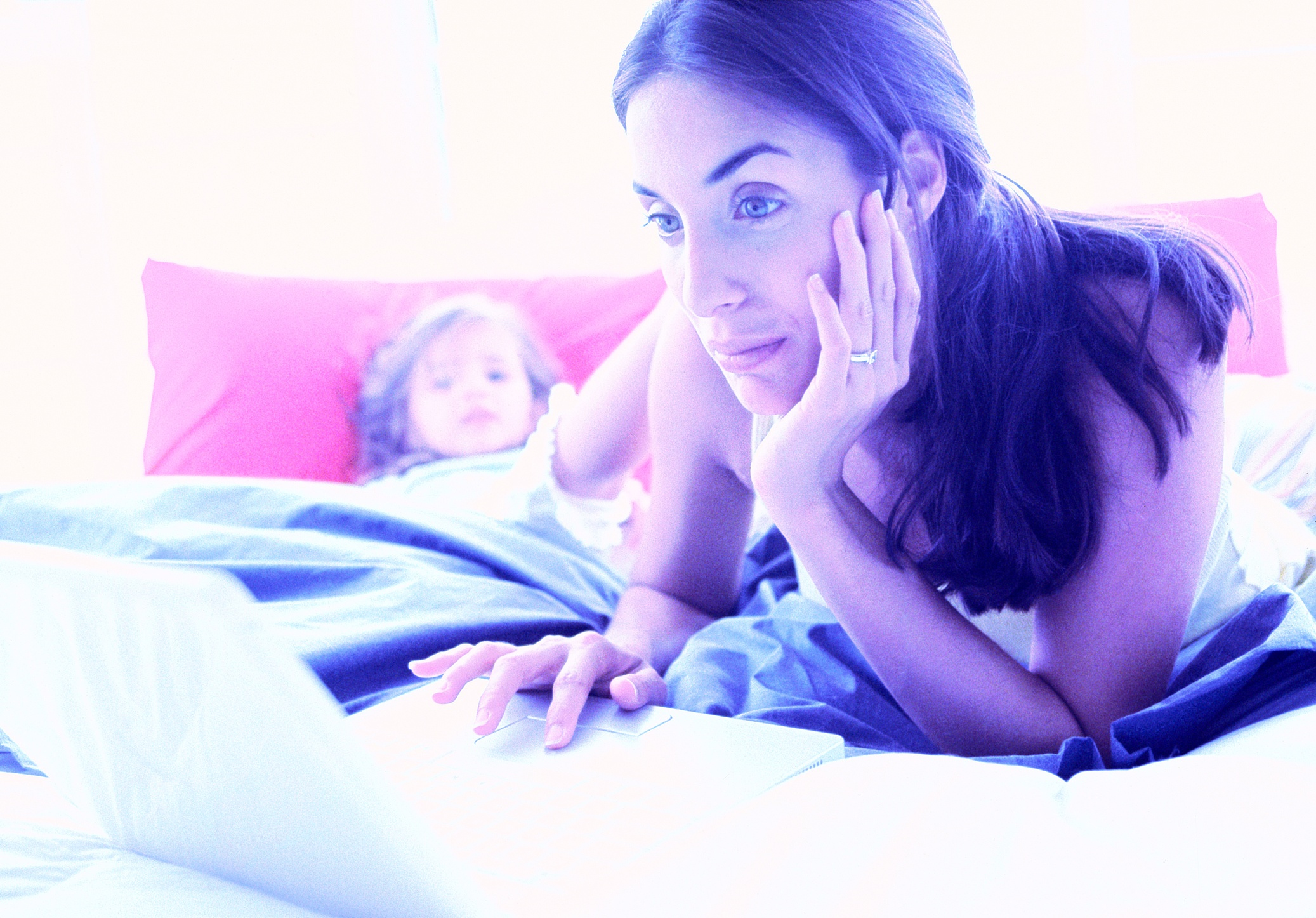 Young mom looking at computer with her child.