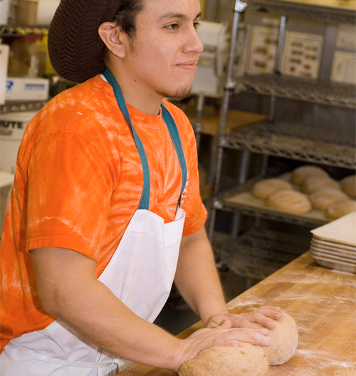 great harvest employee rolling out dough on a table