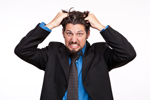 Frustrated young businessman pulling his hair