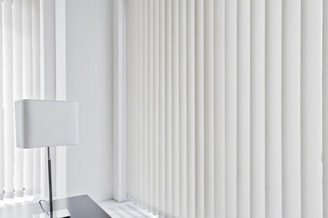 vertical blind in white behind a black lamp