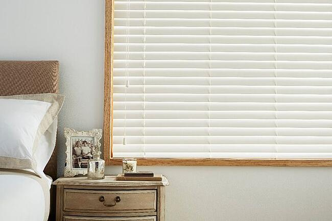 white wooden venetian blind next to bed