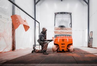 carretilla contrapesada de segunda mano siendo pintada por un técnico