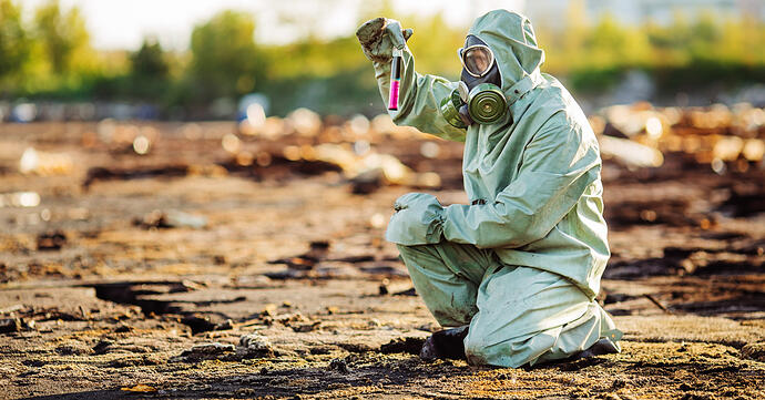 Person crouched down in a Hazmat suit with a gas mask holding a test tube of pink chemicals