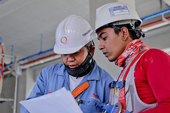 Two men in white hard hats looking at the same piece of paper