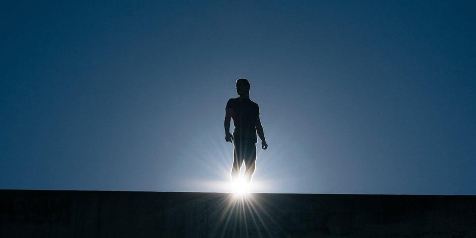 Man standing on a bridge with a sun light beam illuminating him